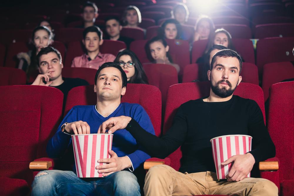 man stealing popcorn at a movie