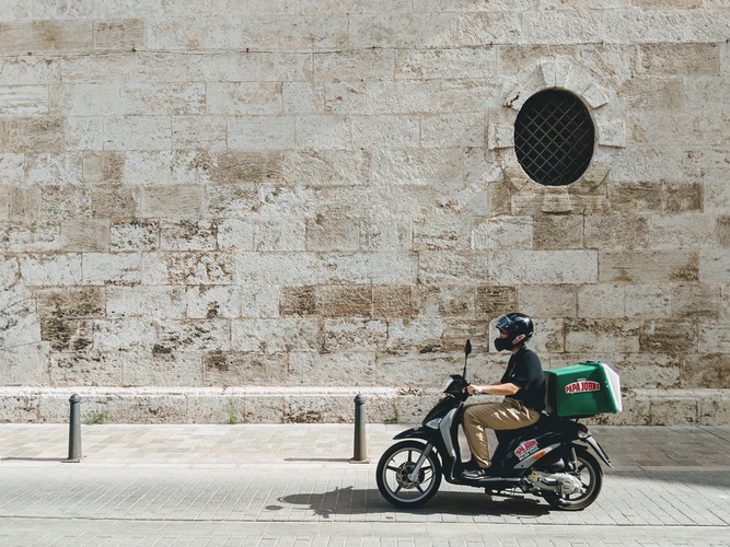 person driving scooter with pizza boxes