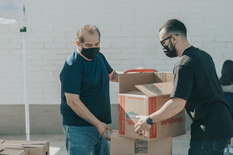 two men arranging stack of boxes