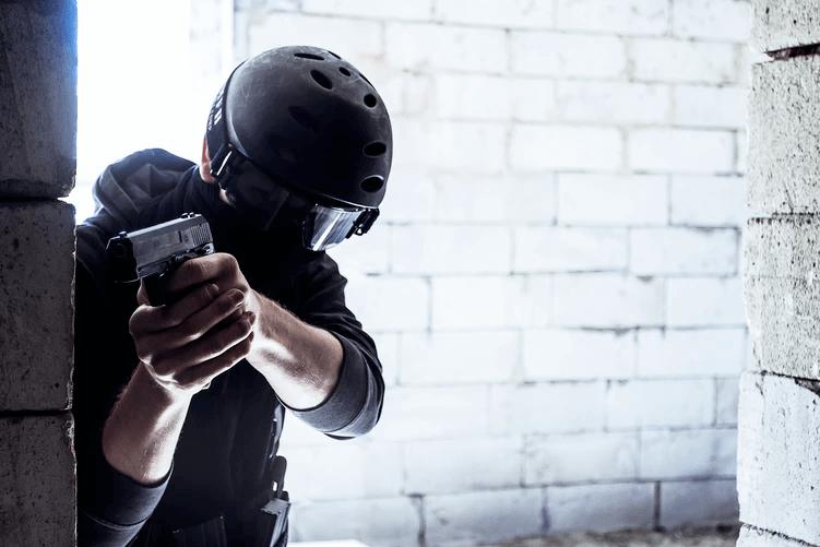 agent looking around corner with gun