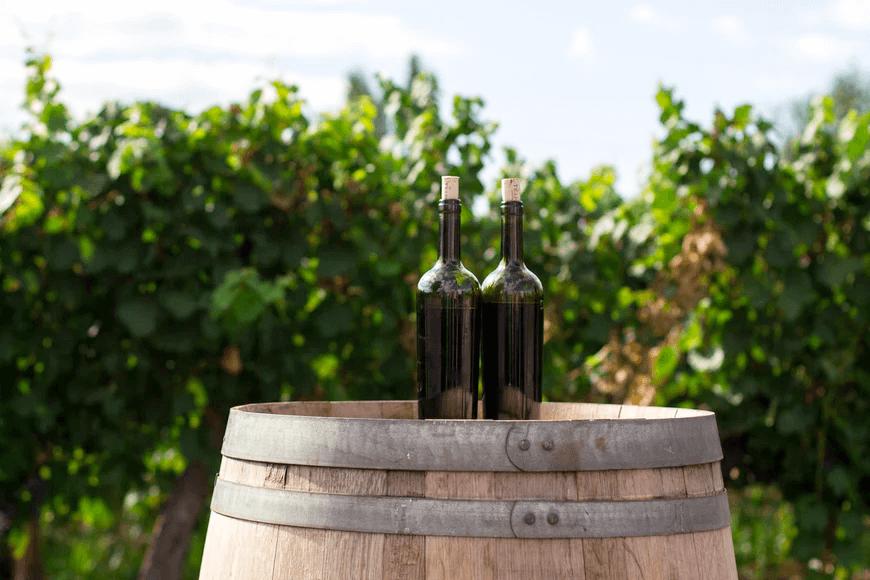 two wine bottles on barrel